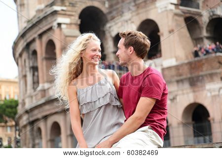 Travel couple in Rome by Coliseum in love. Tourists dating laughing having fun. Two happy young tourist traveling in Italy. Beautiful blonde woman and man in 20s on holidays vacation in Italy, Europe.