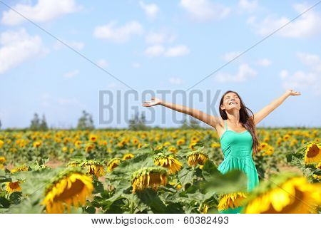 Happy carefree summer girl in sunflower field in spring. Cheerful multiracial Asian Caucasian young woman joyful, smiling with arms raised up.