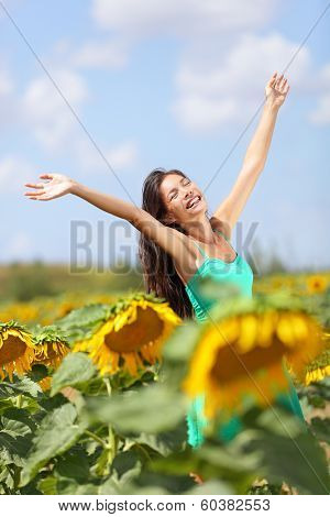 Summer girl happy in sunflower flower field. Cheerful multiracial Asian Caucasian young woman joyful, smiling with arms raised up.