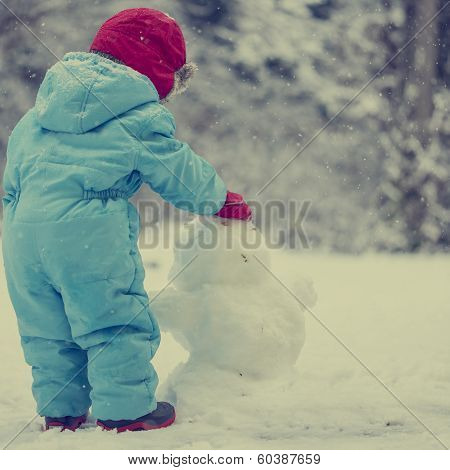 Young Toddler Building A Snow Man