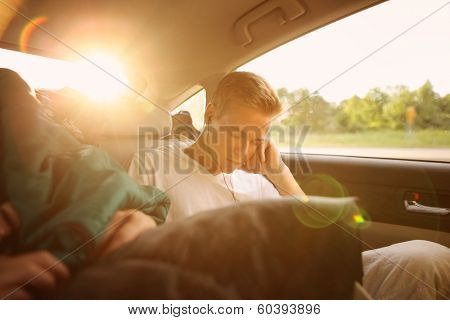 Teenager sleeping in the backseat of a car on a trip