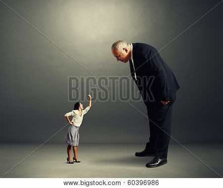 big serious man looking at small angry woman over dark background