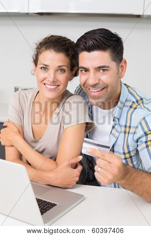 Attractive couple using laptop together to shop online at home in kitchen