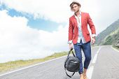 stock photo of stroll  - picture of a young fashion man strolling outdoor with a bag in his hand while looking away from the camera - JPG