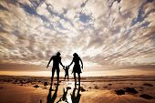 stock photo of father time  - Happy family together hand in hand on the beach at sunset - JPG