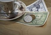 stock photo of pesos  - Cuban pesos and espresso coffee on wood table surface - JPG