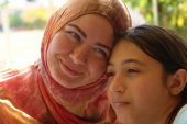 Muslim woman in headscarf and her daughter