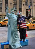 Artist Imitating Statue Of Liberty And Tourist