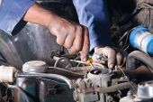 image of auto repair shop  - Closeup of hands of mechanic repairing a vehicle - JPG