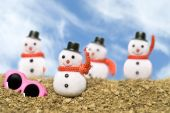 image of inference  - Christmas snowmen ornaments on a gravel beach with pink sunglasses to cast a tropical summer theme - JPG