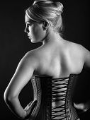 stock photo of corset  - Photo of the back of a beautiful blond woman wearing a leather corset - JPG