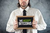 Постер, плакат: Businessman Holding Board With Title We Accept Bitcoins