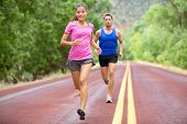 Athletes running - sport couple jogging in summer. Runners jogging in summer on road. Joggers traini