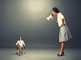 stock photo of angry smiley  - angry young woman screaming at smiley woman on the chair - JPG