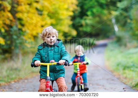 Two Active Brother Boys Driving On Bikes In Autumn Forest