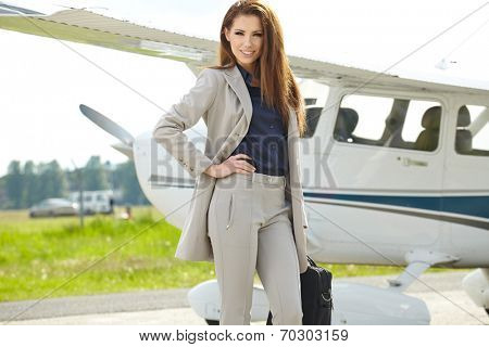 Portrait of wealthy woman with luggage walking against private jet at airport terminal
