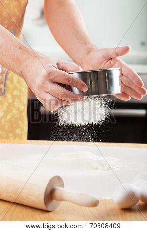 mans hands sifting flour through a sieve for baking