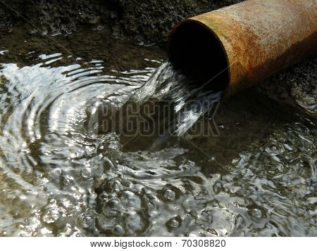 stream of artesian water from the old rusty pipe