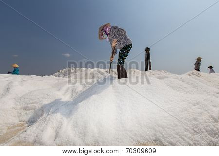 a woman wearning conical hat is raking on the heap of salt at Binh Thuan , Vietnam in daylight