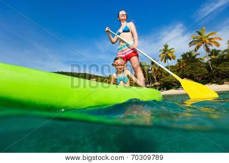 Mother and her adorable little daughter paddling on stand up board having fun during summer beach vacation