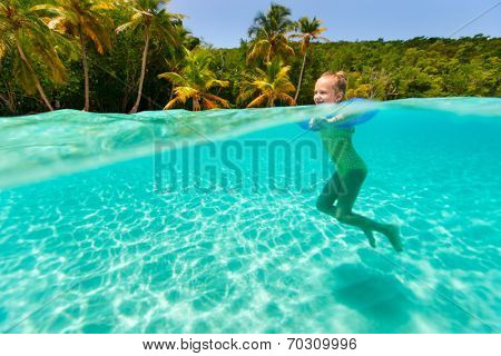 Split underwater photo of adorable little girl with blue inflatable ring swimming in tropical ocean  on summer vacation