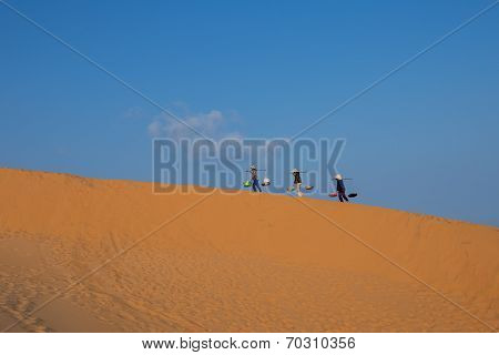 Three hawkers ( saleswomen ) carrying fast foods are walking on the sand hills