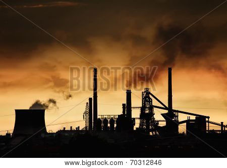 Smokestack in factory with yellow sky and clouds. Industrial pollution.