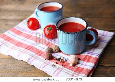 Homemade tomato juice in color mugs, spices and fresh tomatoes on napkin, on wooden background