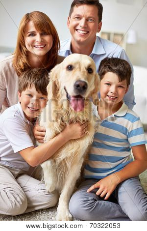Family of four posing with their dog
