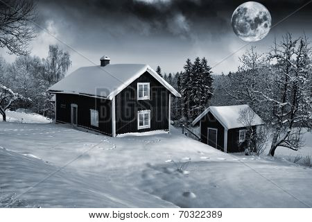 full-moon rising above old cottages draped in a snowy winter landscape, old rural surroundings