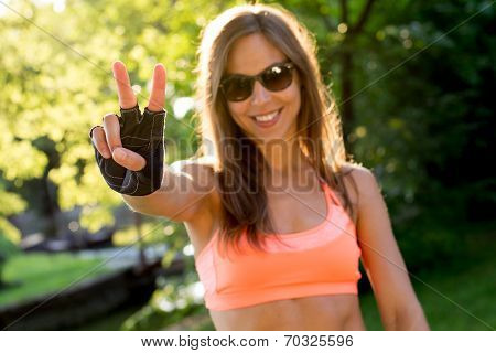 lovely young woman showing victory or peace sign during sport