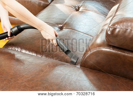 Woman Cleaning Sofa With Vacuum Cleaner