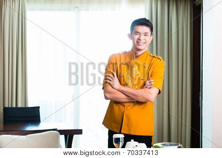 Asian Chinese room service waiter or steward serving guests food in a grand or luxury hotel room