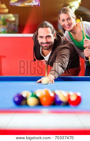 Couple or friends playing billiard with queue and balls on pool table