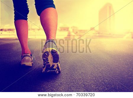 a woman with an athletic pair of legs going for a jog or run during sunrise or sunset - healthy lifestyle concept toned with a retro vintage instagram like filter