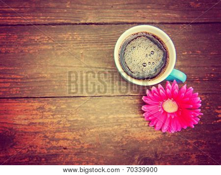 a cup of coffee and a flower on a wooden texture background toned with a retro vintage instagram filter