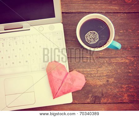 Laptop or notebook with cup of coffee and origami heart on old wooden table toned with a retro vintage instagram filter