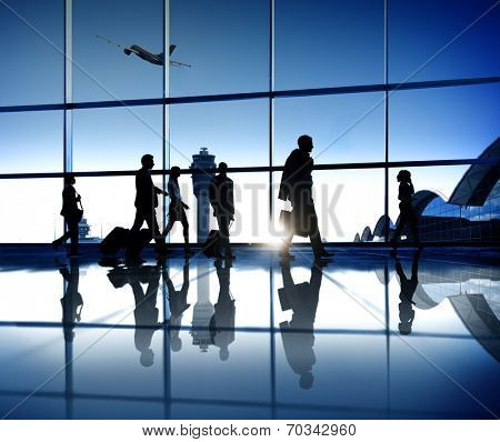 Business people on their way to the business trip walking in an airport