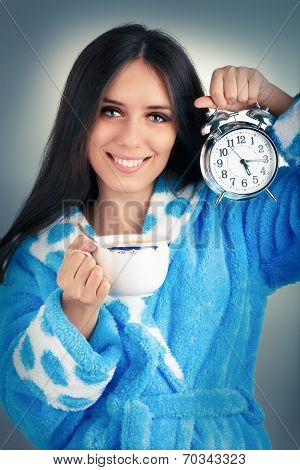 Young Woman in Bathrobe Holding an Alarm Clock and a Cup of Coffee