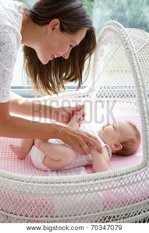 Beautiful Woman Smiling With Newborn Child In Cot
