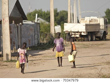 BOR, SOUTH SUDAN-DECEMBER 3 2010: Unidentified children carry containers of water back to their families.