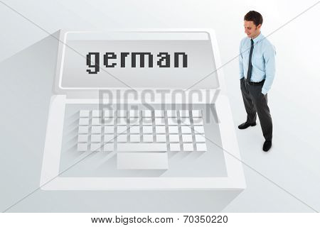 The word german and happy businessman standing with hands in pockets against white laptop