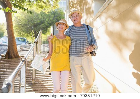 Happy tourist couple walking in the city on a sunny day