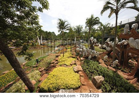 A meadow with owl and trees and stones and grass and flowers in the Nong Nooch tropical botanic gard