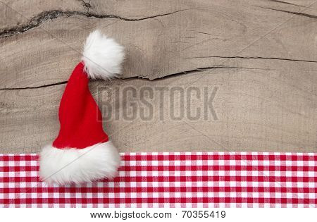 Greeeting Card With Santa Hat On Wooden Background For Christmas