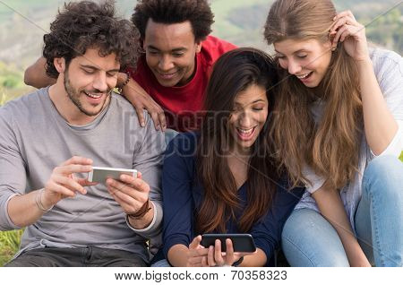 Group Of Laughing Friends With Cellphone Outdoor