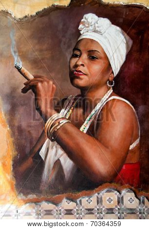 Woman in Aruba wearing a head scarf and traditional jewellery smoking a big fat Cuban cigar with a look of relish and defiance against an old grunge graffiti painted brown wall