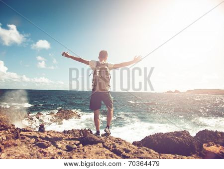 Young man wearing a backpack standing on rocks overlooking the ocean with his arms spread in contemplation backlit by the flare of a hot tropical sun