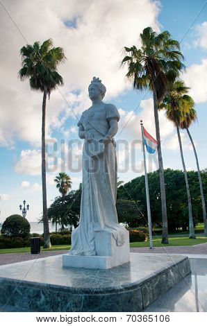 Statue of Queen Wilhelmina in Oranjestad, Aruba with the Dutch flag standing in a square surrounded by tropical palm trees under a sunny cloudy blue summer sky