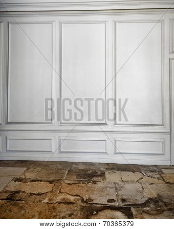 White wooden paneling above a cracked, weathered and worn old flagstone floor in an architectural background